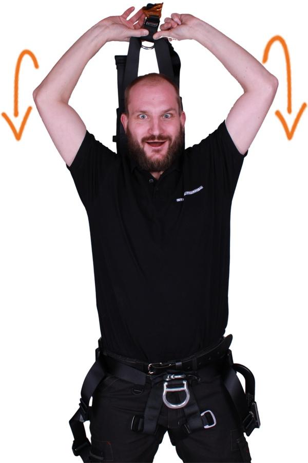 schouderriemen van harnas over hoofd halen
